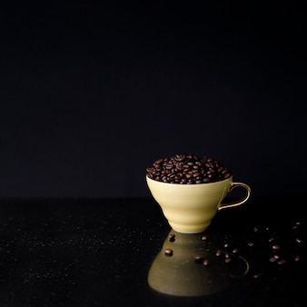 Ceramic cup filled with roasted coffee beans on black background