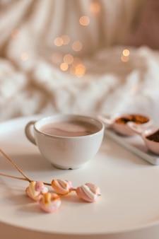 Керамическая чашка горячего шоколада или какао с зефиром на белом столе