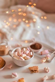 白いテーブルの上にマシュマロとホットチョコレートまたはココアのセラミックカップ