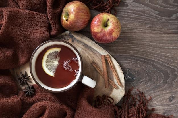 ブラウンウールストールにレモン、リンゴ、アニススター、シナモンを添えたセラミックカップのホットティー。木のテーブルの上。上面図