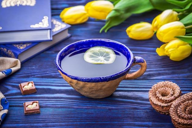 レモンティー、黄色いチューリップ、本のセラミックカップ