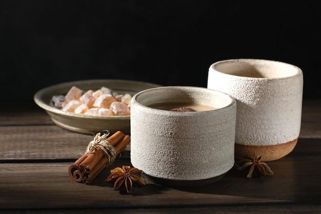 Керамическая чашка чая масала со специями и сахаром на деревянном столе