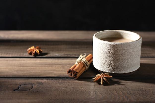 Керамическая чашка чая масала со специями на деревянном столе