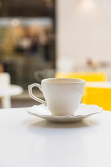 Ceramic cup and saucer on white table against blur background