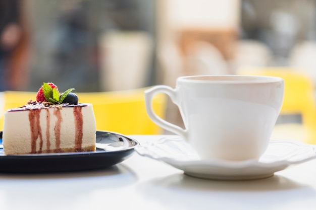 Ceramic cup and saucer with delicious cake slice on white surface