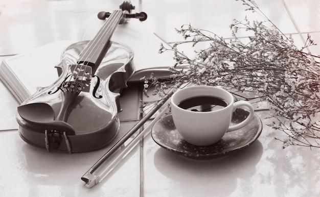 弓の真ん中に置かれたブラックコーヒー、バイオリン、ぼやけた花のセラミックカップ。黒と白のトーン、周りのぼやけた光