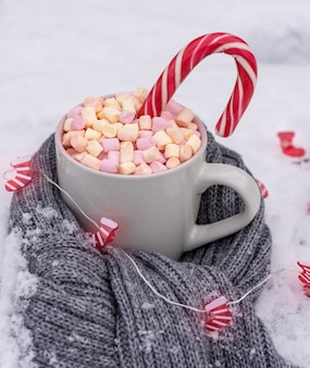 Ceramic cup with hot chocolate with marshmallows on white snow wrapped in a gray scarf