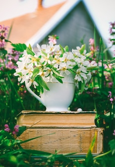 Ceramic cup with white flowers on a pile of old books in a clearing with flowering herbs against the backdrop of a village house