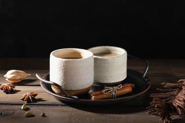 Керамические чашки чая масала со специями на деревянном столе