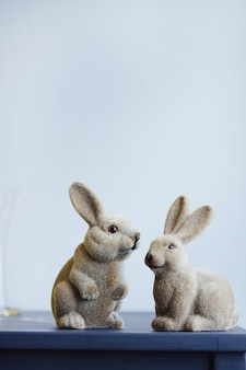 セラミックイースターは灰色の壁の背景にヴィンテージの置物のウサギをうさぎ