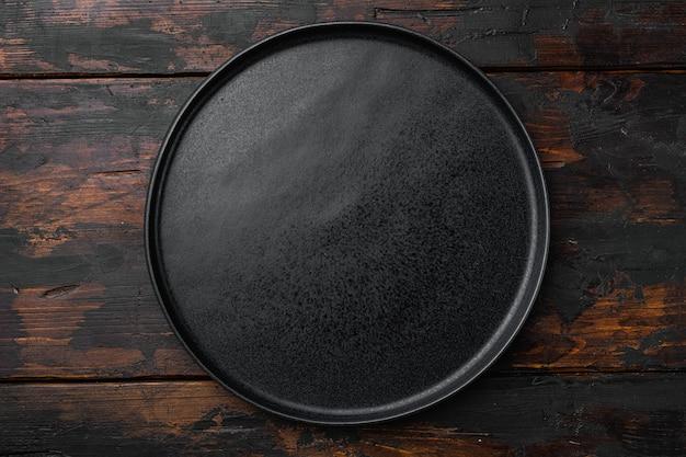 오래 된 어두운 나무 테이블 배경에 세라믹 빈 검은 접시 세트