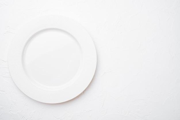 텍스트 또는 음식을 위한 복사 공간이 있는 복사 공간이 있는 세라믹 빈 흰색 접시, 흰색 석재 테이블 배경 위에 있는 평면도
