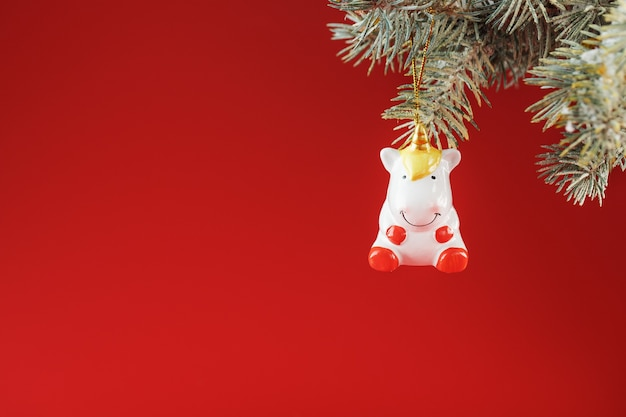Ceramic figure of a unicorn on a spruce branch, on a red background.