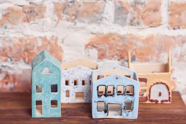 벽돌 벽에 지붕이없는 집의 세라믹 인물. 수공.