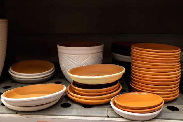 Ceramic flowerpot trays in the shape of saucers on a garden store shelf. clay products of various sizes and colors.