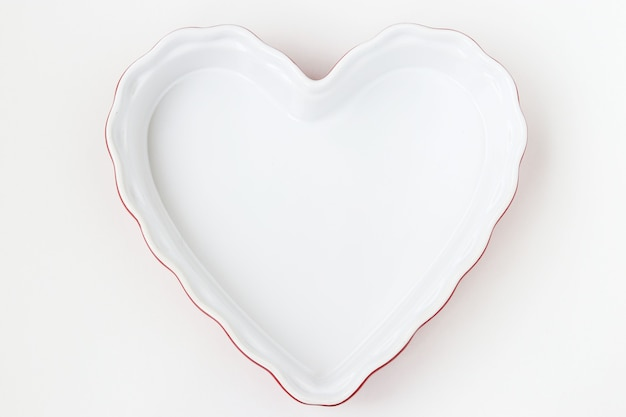 Ceramic form in the form of a heart is located on a white background, top view