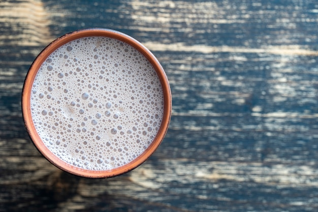 Ceramic glass of chocolate milkshake on wooden