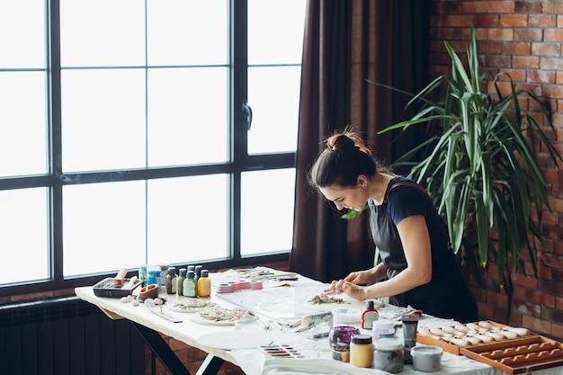 セラミックの手工芸品。進行中のアートワーク。朝の日光のインスピレーション。モデリングツールを持つ若い女性