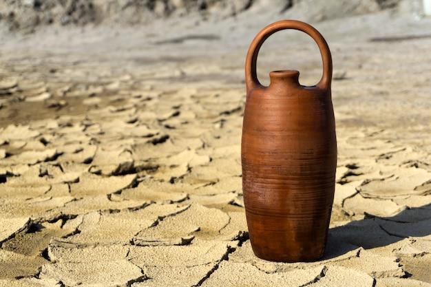 물이 담긴 세라믹 주전자는 갈라진 마른 진흙 사막 한가운데 서 있다
