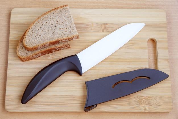 나무 도마에 검은 색 손잡이가있는 세라믹 나이프