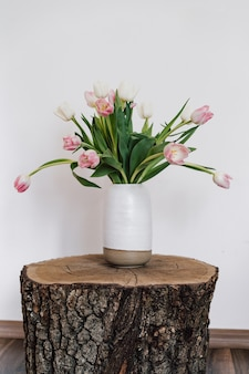 Ceramic light vase with spring tulips on an unusual bedside table