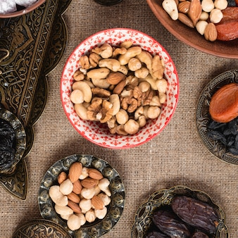 Ceramic and metallic bowl with organic nuts on tablecloth