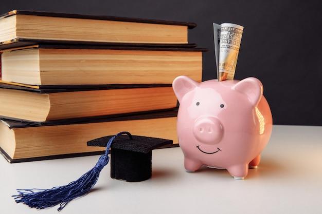 Керамическая копилка со стопкой книг и колпачком. колледж, выпускник, образование, концепция сбережений.