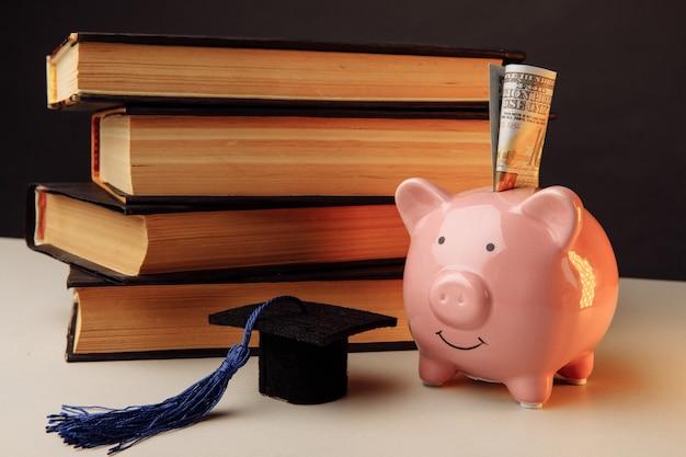 Керамическая копилка со стопкой книг. колледж, выпускник, концепция образования.