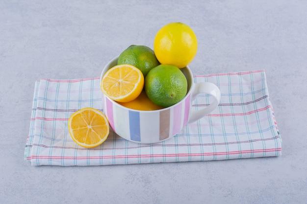 Ceramic mug of fresh juicy lemons on stone.