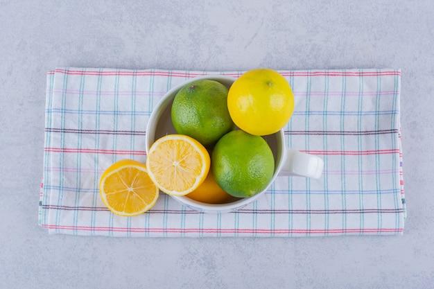 Керамическая кружка свежих сочных лимонов на камне.