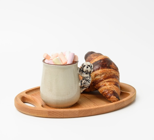 Ceramic mug with cocoa and marshmallows, baked croissant on a wooden serving plate, food on white background