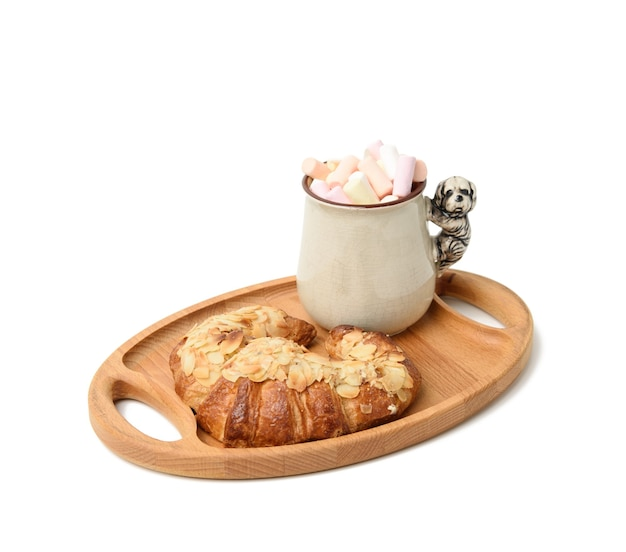 Ceramic mug with cocoa and marshmallows, baked croissant on a wooden serving plate, food on white surface
