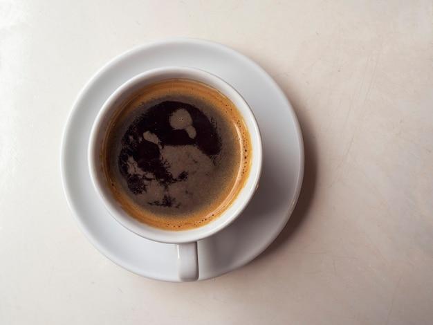 뜨거운 음료와 함께 세라믹 머그, 나무 테이블에 블랙 커피. 커피 한잔과 함께 간단한 구성입니다. 아침 기분.