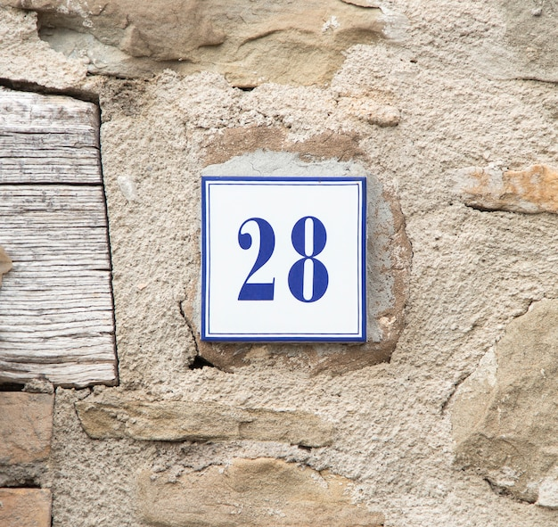 Ceramic number twenty eight on the grey stone wall