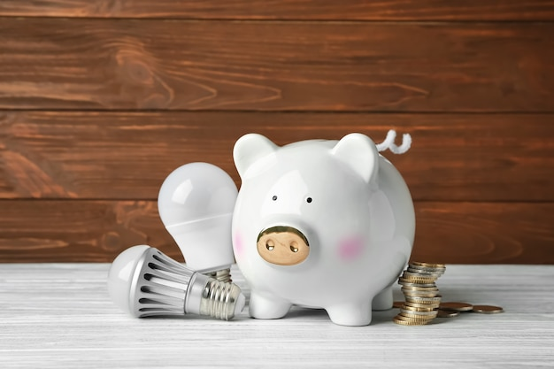 Ceramic piggy bank with light bulbs and coins on wooden table