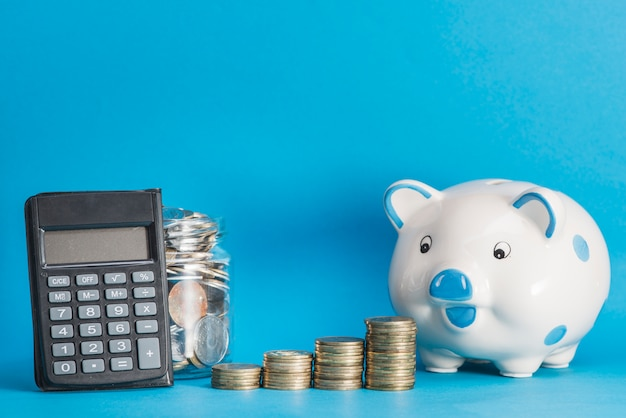Ceramic piggybank; calculator; glass jar and stack of coins against blue background