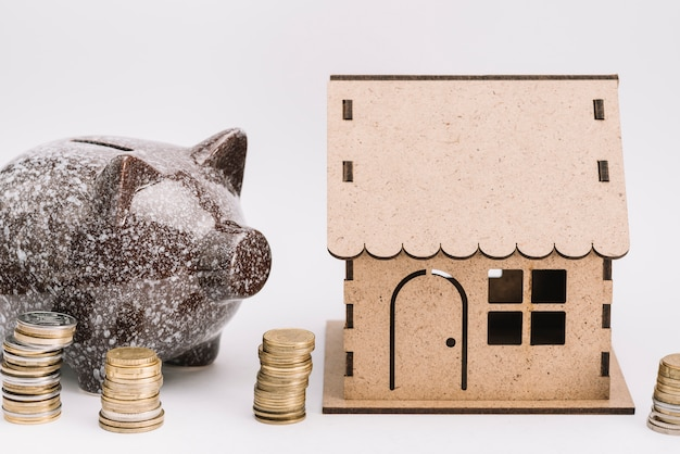 Ceramic piggybank with stack of coins near the cardboard house on white background