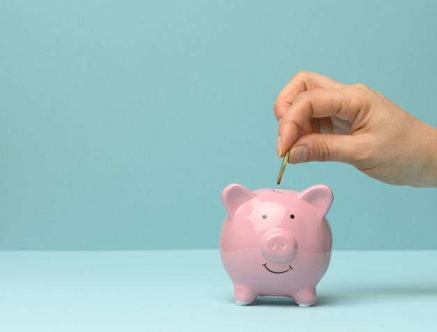 세라믹 핑크 돼지 저금통과 손 안에 동전을 던지고, 금융 저축 개념, 복사 공간
