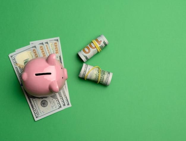 Керамическая розовая копилка и бумажные американские доллары сша на зеленом фоне