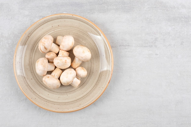 Ceramic plate of fresh uncooked mushrooms on stone table.