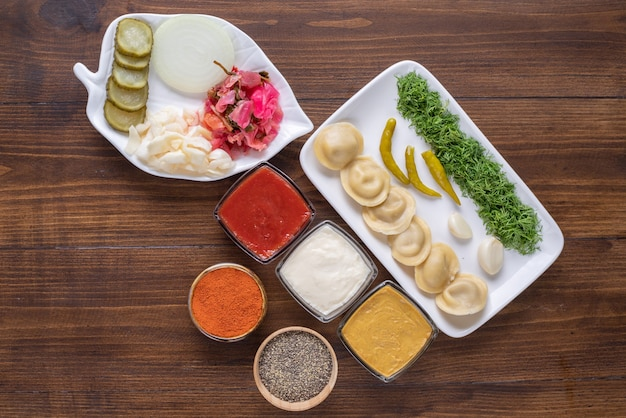 Ceramic plate full of homemade dumplings and pickles on wooden surface.