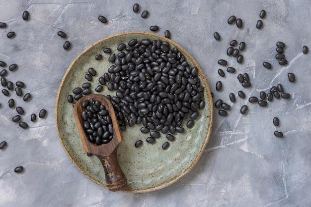 ネガティブスペースのある灰色のテーブルトップビューに木製のスクープが付いた乾燥黒豆でいっぱいのセラミックプレート。健康的な食事と菜食主義の概念。伝統的なラテンアメリカのいとこ成分