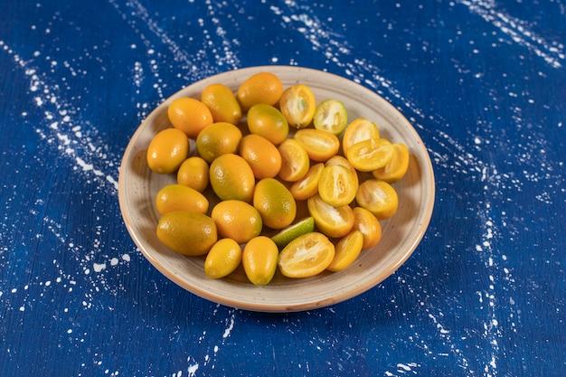 Керамическая тарелка нарезанных свежих фруктов кумквата на мраморной поверхности
