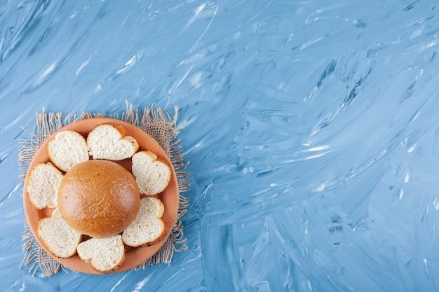 파란색 표면에 얇게 썬된 흰 토스트 빵의 세라믹 플레이트.