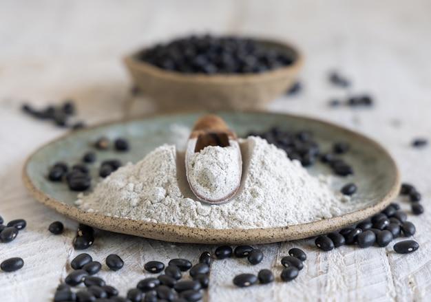 Керамическая тарелка с мукой черной фасоли и сушеной фасолью с крупным планом деревянной ложкой. здоровое питание и вегетарианская концепция. традиционный латиноамериканский кузен ингредиент