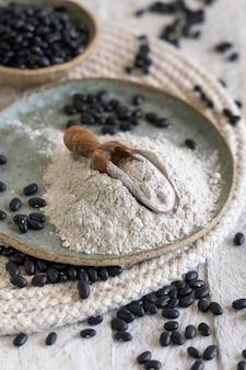 黒豆粉と木のスプーンのクローズアップと乾燥豆のセラミックプレート。健康的な食事と菜食主義の概念。伝統的なラテンアメリカのいとこ成分