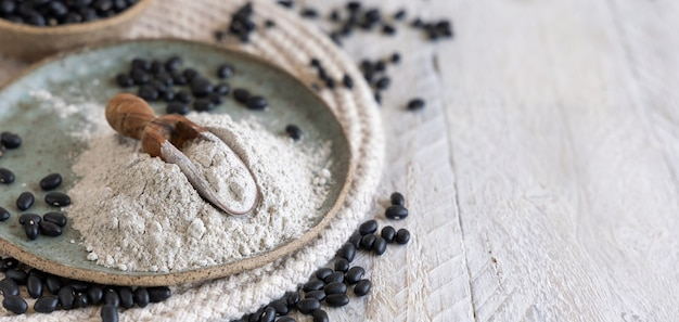黒豆粉と乾燥豆のセラミックプレートとコピースペースのある木のスプーンのクローズアップ。健康的な食事と菜食主義の概念。伝統的なラテンアメリカのいとこ成分