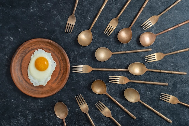 Ceramic plate with fried egg and brass forks and spoons look like sperm competition. spermatozoons floating to ovule. top view,flat lay.