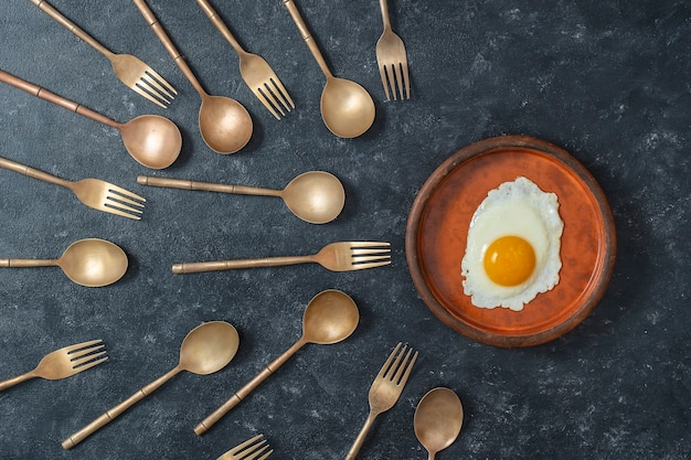 Ceramic plate with fried egg and brass forks and spoons look like sperm competition
