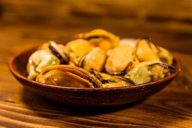素朴な木製のテーブルの上に準備されたムール貝とセラミックプレート